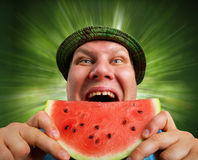 Bizarre man eating watermelon. Outdoors in summer stock image