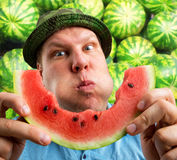 Bizarre man eating watermelon. Outdoors in summer royalty free stock photos