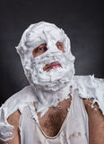 Bizarre man with face completely in shaving foam. Thinks over grey Royalty Free Stock Photo