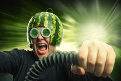 Bizarre man in a helmet from a watermelon. Riding fast stock photography