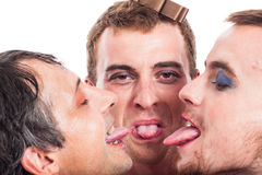 Bizarre men sticking out tongue. Close up of three bizarre transvestites sticking out tongue, isolated on white background stock photography