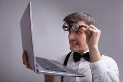 Bizarre Mens die Laptop bekijken stock afbeelding