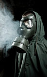 Bizarre portrait of man in gas mask. On smoky industrial background with pipes after nuclear disaster Royalty Free Stock Image