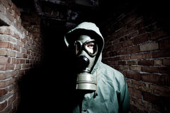 Bizarre portrait of man in gas mask. On smoky industrial background with pipes after nuclear disaster Royalty Free Stock Images
