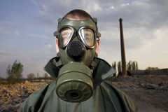 Bizarre portrait of man in gas mask. On smoky industrial background with pipes after nuclear disaster stock photos