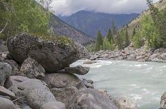 "Bizarre stone on the shore of a mountain river.  Altai Mountains. Bizarre stone on the shore of a mountain river. Rapids ""Atlantes"" on the river Argut.  Altai Royalty Free Stock Photos"