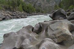 """Bizarre stone on the shore of a mountain river.  Altai Mountains. Bizarre stone on the shore of a mountain river. Rapids """"Atlantes"""" on the river Argut.  Altai Stock Photos"""