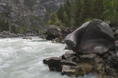 """Bizarre stone on the shore of a mountain river.  Altai Mountains. Bizarre stone on the shore of a mountain river. Rapids """"Atlantes"""" on the river Argut.  Altai Stock Images"""