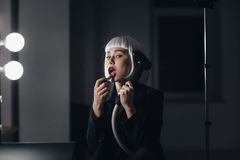 Bizarre woman holding steamer and applying lipstick in dressing room Stock Images
