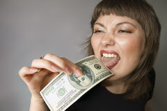 Bizarre woman. Taste of the money. Woman with hand of $100 and it licks by the tongue Stock Images