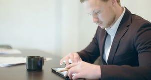 Biznes - Atrakcyjny biznesowy mężczyzna używa cyfrową pastylkę zbiory