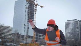 Biznes, budynek, papierkowa robota i ludzie pojęć, - szczęśliwy budowniczy w hardhat z schowkiem przy budową zbiory