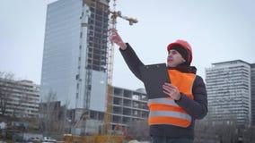 Biznes, budynek, papierkowa robota i ludzie pojęć, - szczęśliwy budowniczy w hardhat z schowkiem przy budową zbiory wideo