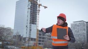Biznes, budynek, papierkowa robota i ludzie pojęć, - szczęśliwy budowniczy w hardhat z schowkiem przy budową zdjęcie wideo