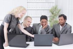 Biznes drużyna dyskutuje biznesowych zagadnienia siedzi przy ich biurkiem obraz stock