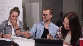 Biznes drużyna dyskutuje projekt lub pomysł Młody człowiek w szkłach i dwa kobietach w przypadkowym obsiadaniu przy biuro stołem  zdjęcie wideo