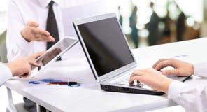 Biznes drużyna obchodzi się pieniężne mapy na laptopie i pastylce Obrazy Stock
