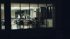 Biznes drużyna opowiada, dzwoni i pracuje z papierami robi akcydensowej nocnej zmianie jest ruchliwie z naglącą pracą, Widok od o zdjęcie wideo