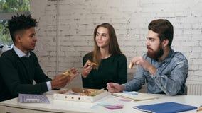 Biznes drużyna rozochoceni młodzi ludzie cieszy się pizzę wpólnie w biurze, opowiadają mieć zabawy udzielenia lunch zbiory wideo