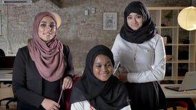 Biznes drużyna trzy młodej muzułmańskiej kobiety patrzeje w kamerze i ono uśmiecha się w nowożytnym biurze w hijab zbiory