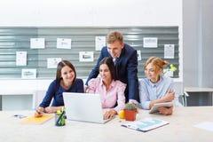 Biznes drużyna w nowożytnym jaskrawym biurowym wnętrzu przy pracą na laptopie zdjęcie royalty free