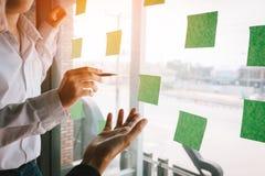 Biznes drużyna wskazuje pomysły na adhezyjnym n z szklanym deskowym pokojem obrazy stock