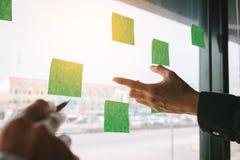 Biznes drużyna wskazuje pomysły na adhezyjnym n z szklanym deskowym pokojem zdjęcia stock