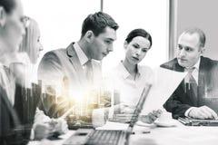 Biznes drużyna z laptopem i papierami przy biurem zdjęcia stock