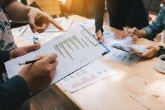 Biznes drużynowa dyskusja o koszt firmie pracuje wpólnie i wskazuje papierowego zbiorczego wykres zdjęcie stock