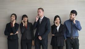 Biznes drużyny ludzie stoi używać mądrze telefon w nowożytnym biurze Obrazy Royalty Free