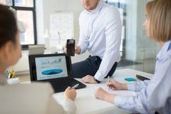Biznes dru?yna z smartphone pracuje przy biurem zdjęcie royalty free