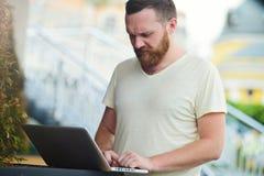 Biznes i wolność Mężczyzna z brodą za laptopem w mieście, uwalnia stylowego, nowożytnego biznes, Obraz Royalty Free