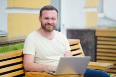 Biznes i wolność Mężczyzna z brodą za laptopem w mieście, uwalnia stylowego, nowożytnego biznes, Zdjęcia Royalty Free