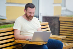 Biznes i wolność Mężczyzna z brodą za laptopem w mieście, uwalnia stylowego, nowożytnego biznes, Zdjęcie Royalty Free