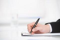 Biznes notatki. Zakończenie ręki writing coś w nutowym ochraniaczu Obraz Stock