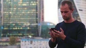 Biznes, technologia i ludzie pojęć, - uśmiechnięty biznesmen z smartphone nad budynkiem biurowym zbiory
