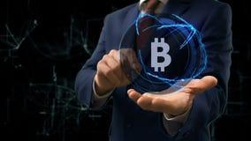 Biznesmenów przedstawień pojęcia holograma znak BTC na jego ręka zbiory