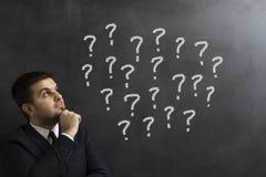 Biznesmenów przyglądający znaki zapytania na blackboard Zdjęcie Stock