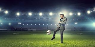 biznesmen bawić się piłkę nożną Mieszani środki obraz stock
