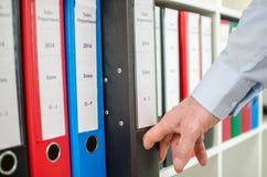 Biznesmen bierze out segregatoru od półki Obrazy Stock