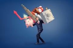 Biznesmen chodzi pod waga ciężką wiele rzeczy na jego ramionach: bezpieczny pudełko, prosiątko bank, drapacz chmur i zdjęcie royalty free
