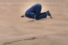 Biznesmen chuje jego kierowniczego w piasku ucieka od problemów zdjęcie stock