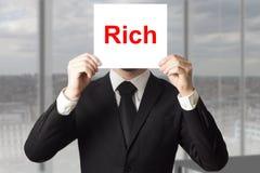 Biznesmen chuje twarz za szyldowym bogactwem Obraz Royalty Free