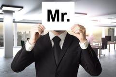 Biznesmen chuje twarz za szyldowym mister zdjęcia stock