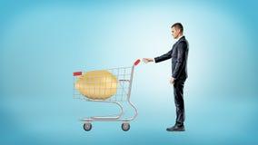 Biznesmen chwyta metalu wózek na zakupy z ogromnym złotym jajkiem przechującym inside Zdjęcia Royalty Free