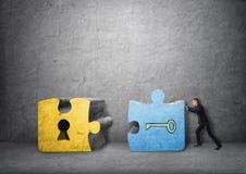 Biznesmen ciągnie wpólnie klucza i keyhole kawałki wyrzynarki łamigłówka obraz stock
