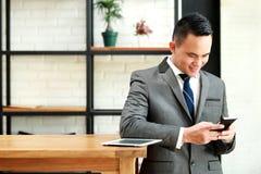 Biznesmen cieszy się texting na telefonie komórkowym Fotografia Stock