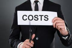 Biznesmen ciie słowo koszty na papierze z nożycami Fotografia Stock
