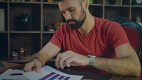 Biznesmen czyta biznesowych papiery w biurze Badacz rynku analizuje papier zbiory wideo