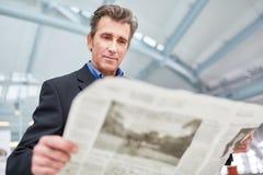 Biznesmen czyta dziennika w lotnisku zdjęcie royalty free
